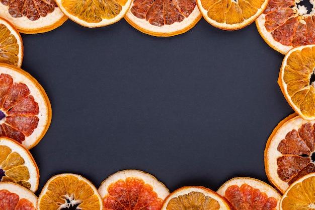 Vista superior de uma moldura feita de fatias secas de laranja e toranja, dispostas em fundo preto, com espaço de cópia