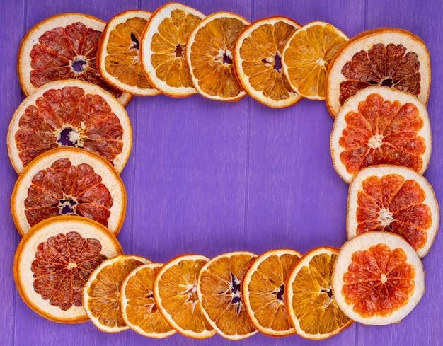Vista superior de uma moldura feita de fatias secas de laranja e toranja, dispostas no fundo de madeira roxo com espaço de cópia