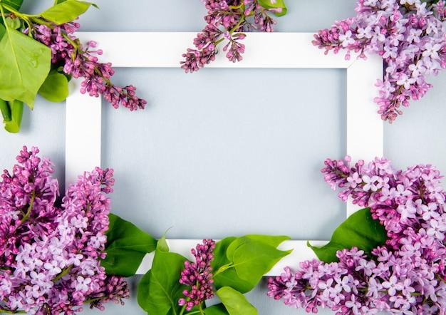 Vista superior de uma moldura vazia com flores lilás sobre fundo branco, com espaço de cópia