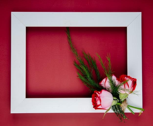 Vista superior de uma moldura vazia com pequeno buquê de rosas de cor vermelha com erva-doce em fundo vermelho, com espaço de cópia