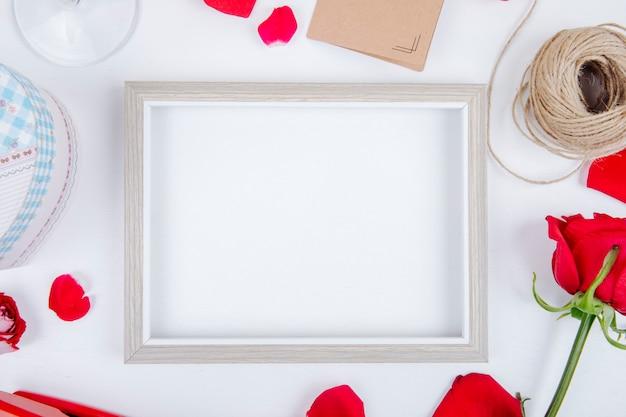 Vista superior de uma moldura vazia com uma bola de caixa de presente de rosas de cor vermelha de corda pequeno cartão postal em fundo branco, com espaço de cópia