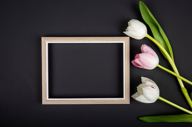 Vista superior de uma moldura vazia e tulipas de cor branca e rosa na mesa preta com espaço de cópia