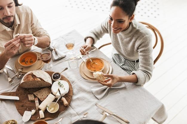 Vista superior de uma mulher afro-americana sorridente, sentada à mesa, tomando sopa de creme com uma fatia de pão na mão