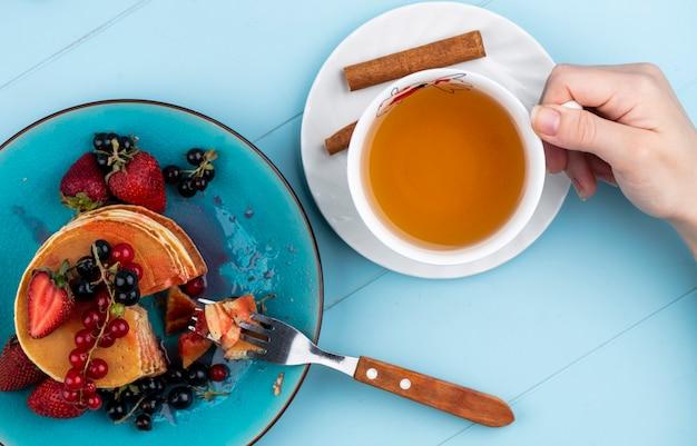 Vista superior de uma mulher bebe uma xícara de chá com panquecas com morangos e groselha vermelha e preta em uma superfície azul