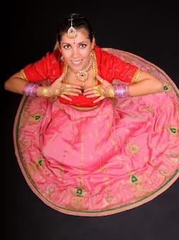 Vista superior de uma mulher branca caucasiana sorridente, sentada em traje tradicional indiano e segurando as mãos perto do peito. fundo escuro
