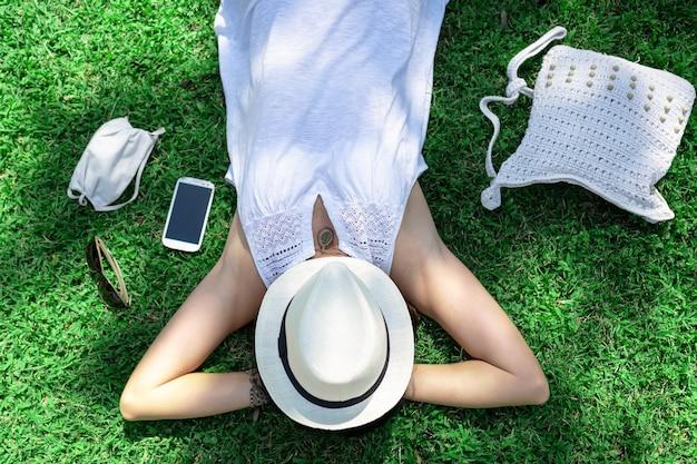 Vista superior de uma mulher caucasiana, deitada em um campo verde do parque