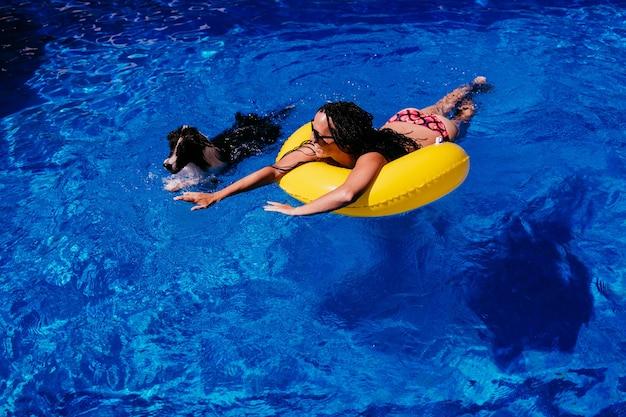 Vista superior de uma mulher caucasiana feliz relaxando em donuts amarelos infláveis na piscina. cão bonito do border collie na piscina. horário de verão, férias e estilo de vida