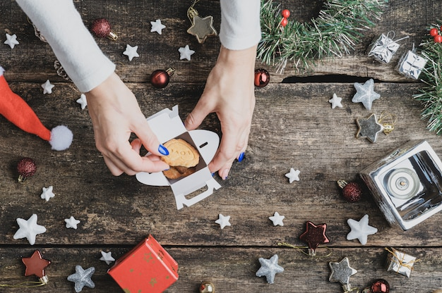 Vista superior de uma mulher colocando biscoitos de férias em uma caixa de mini presente na mesa de madeira rústica