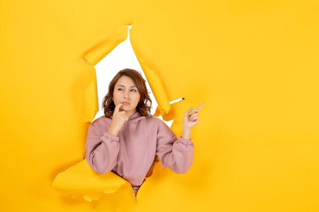 Vista superior de uma mulher confusa apontando algo e espaço livre em amarelo rasgado