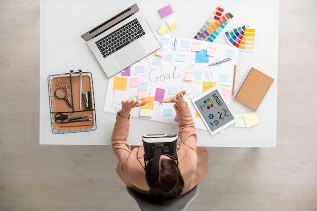 Vista superior de uma mulher criativa com fone de ouvido vr preparando a apresentação enquanto está sentada à mesa com dispositivos móveis, paletas e material de escritório