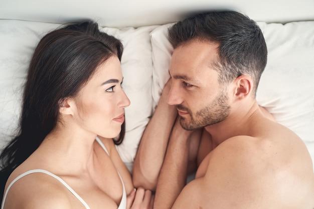 Vista superior de uma mulher de cabelos escuros e seu lindo marido olhando ternamente um para o outro