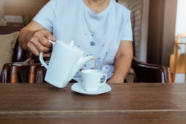 Vista superior de uma mulher derramando chá na mesa de madeira