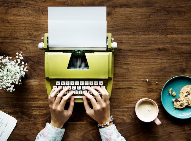 Vista superior de uma mulher digitando em um papel em branco de uma máquina de escrever retrô