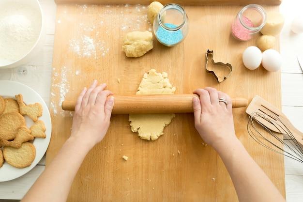 Vista superior de uma mulher enrolando massa para biscoitos com rolo de madeira