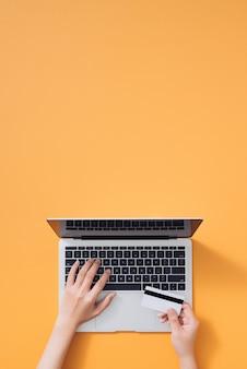 Vista superior de uma mulher fazendo compras on-line usando um laptop com cartão de crédito