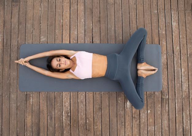 Vista superior de uma mulher fazendo ioga ao ar livre