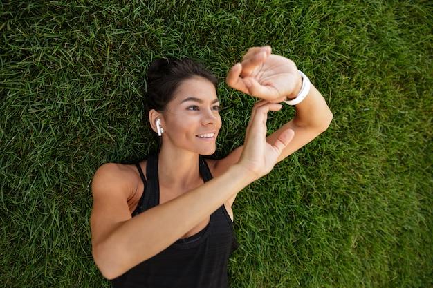 Vista superior de uma mulher feliz fitness em fones de ouvido