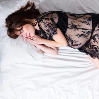 Vista superior de uma mulher grávida feliz em lingerie de renda preta dormindo na cama - copie o espaço