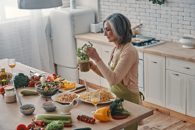 Vista superior de uma mulher idosa de avental cozinhando um jantar saudável enquanto passa um tempo em casa