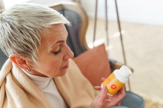 Vista superior de uma mulher idosa focada lendo uma inscrição no frasco de comprimidos