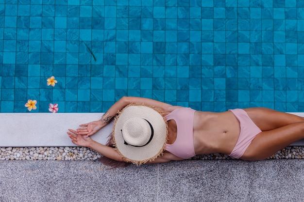 Vista superior de uma mulher magra de biquíni à beira da piscina aproveitando as férias