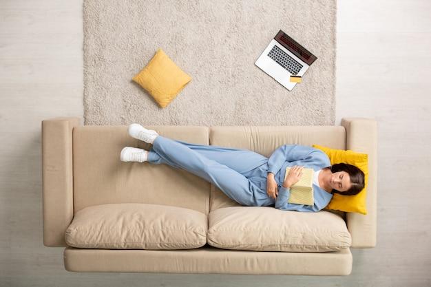 Vista superior de uma mulher repousante de pijama azul cochilando com o livro aberto no peito enquanto está deitada no sofá com a cabeça no travesseiro amarelo depois do trabalho