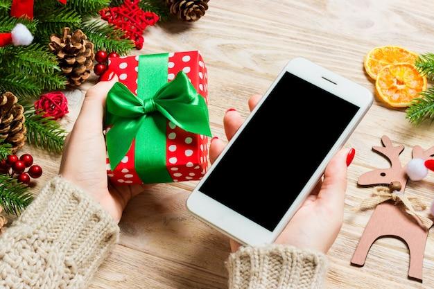 Vista superior de uma mulher segurando um telefone em uma mão e um presente. árvore do abeto e decorações do feriado. conceito de férias de natal.