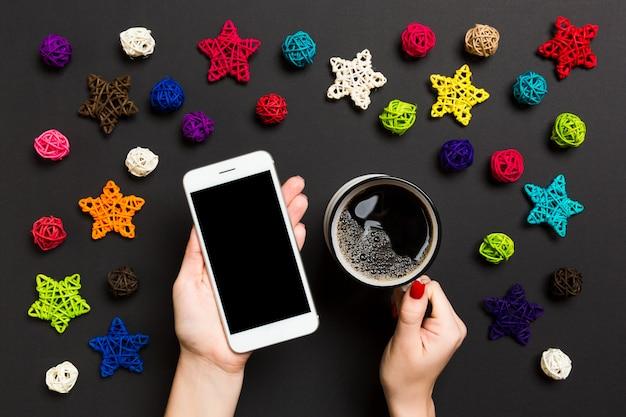 Vista superior de uma mulher segurando um telefone em uma mão e uma xícara de café em outra mão no preto.