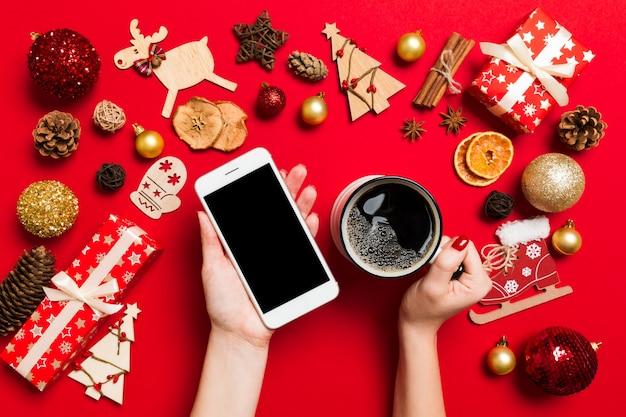 Vista superior de uma mulher segurando um telefone em uma mão e uma xícara de café em outra mão no vermelho