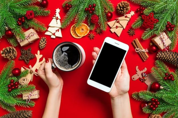 Vista superior de uma mulher segurando um telefone em uma mão e uma xícara de café na outra mão. decorações de natal e brinquedos.