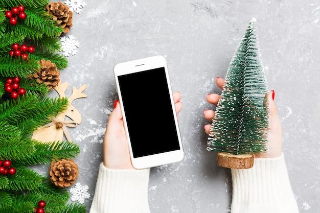Vista superior de uma mulher segurando um telefone na mão em cimento, abeto e decorações festivas. conceito de férias de natal.