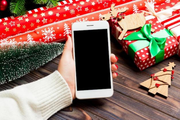 Vista superior de uma mulher segurando um telefone na mão no fundo de madeira de natal