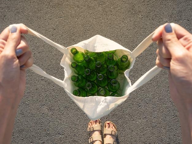 Vista superior de uma mulher segurando uma sacola de pano com garrafas de vidro, conceito de reciclagem, fundo de asfalto, foco seletivo e espaço de cópia