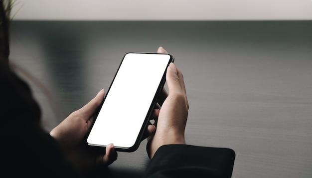 Vista superior de uma mulher segurando uma simulação de tela em branco de um telefone celular