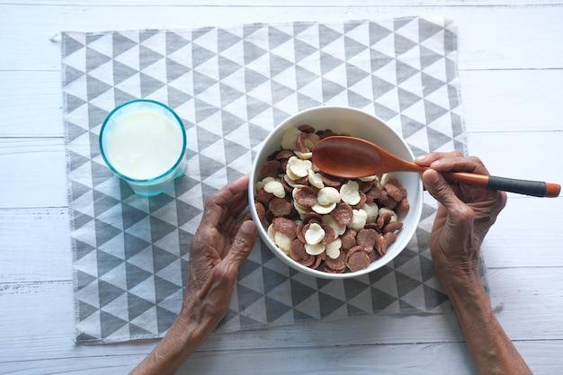 Vista superior de uma mulher sênior comendo flocos de milho de chocolate em uma tigela