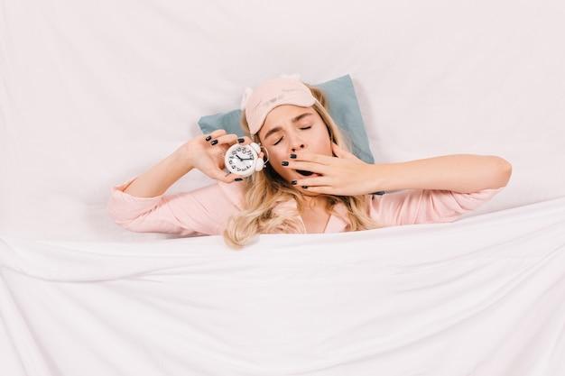 Vista superior de uma mulher sonolenta bocejando na cama