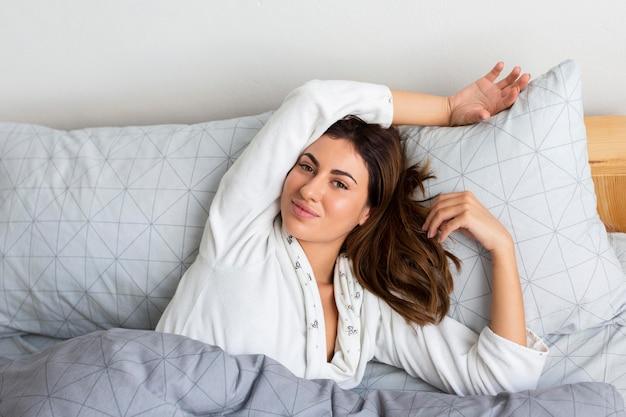 Vista superior de uma mulher sorridente na cama de pijama