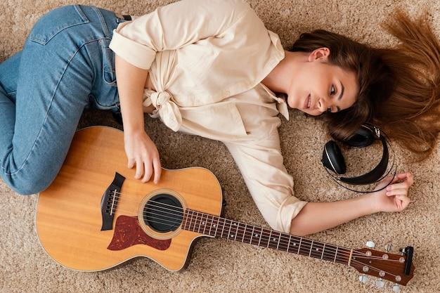 Vista superior de uma musicista em casa no chão com fones de ouvido e violão