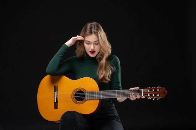 Vista superior de uma musicista segurando uma guitarra e olhando para baixo no preto