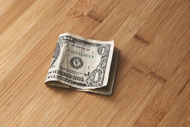 Vista superior de uma nota de um dólar americano em uma superfície de madeira