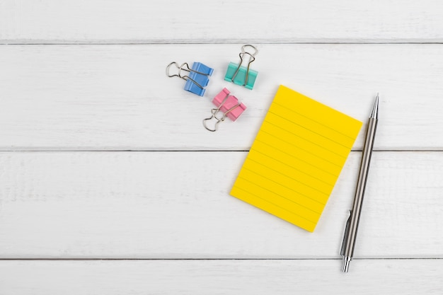 Vista superior de uma nota em branco com lápis e clipes de papel