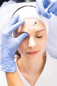 Vista superior de uma paciente deitada com os olhos fechados durante o tratamento de mesoterapia
