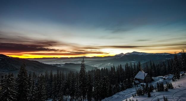 Vista superior de uma paisagem pitoresca deslumbrante de uma casa de campo entre uma floresta de montanhas, colinas e árvores no inverno