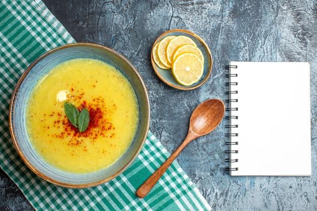 Vista superior de uma panela azul com sopa saborosa servida com hortelã e pimenta ao lado do caderno espiral de colher de pau de limão picado sobre fundo azul