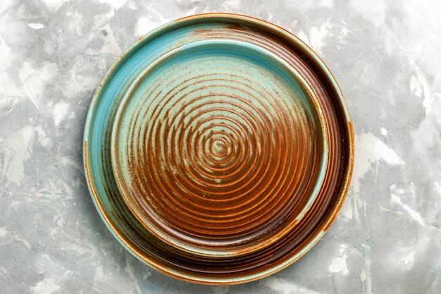 Vista superior de uma panela marrom redonda vazia isolada em uma superfície cinza clara