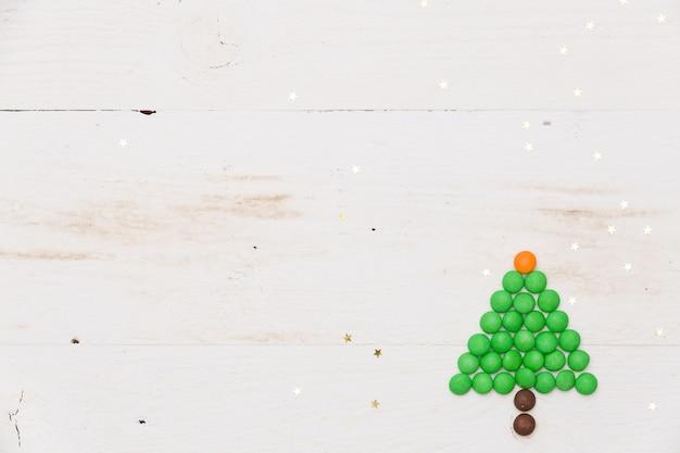 Vista superior de uma pequena árvore de natal engraçada feita de doces com confetes de estrelas douradas na mesa de madeira