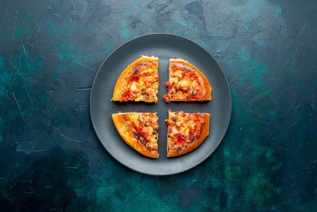 Vista superior de uma pequena pizza de queijo fatiada dentro do prato na superfície azul escura