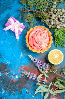 Vista superior de uma pequena torta com um galho de árvore de creme de confeiteiro rosa fatia de limão na superfície azul