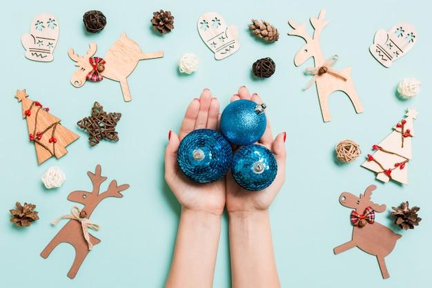 Vista superior de uma pilha de bolas de ano novo nas mãos femininas no backround azul