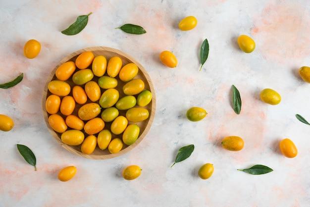 Vista superior de uma pilha de kumquats em uma placa de madeira sobre uma superfície colorida